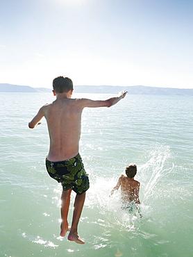 Boys (10-11,12-13) jumping into lake