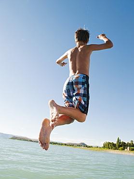 Boy (12-13) jumping into lake
