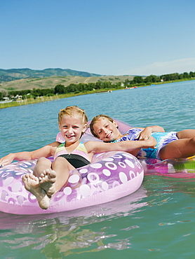 Girls (6-7,8-9) floating on inflatable toys
