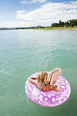 Girl (6-7) floating on inflatable ring