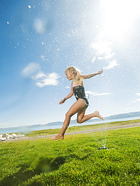 Girl (8-9) jumping over watering system