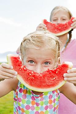 Girls (6-7,8-9) eating watermelon