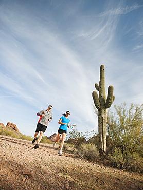 USA, Arizona, Phoenix, Mid adult man and young woman jogging on desert