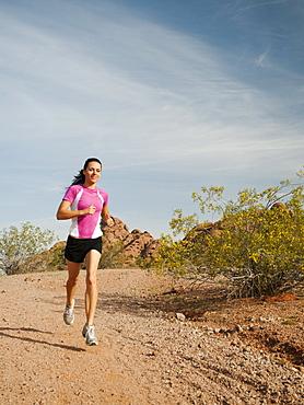 USA, Arizona, Phoenix, Young woman jogging on desert
