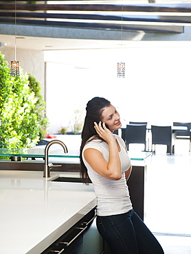 Young woman using mobile phone in her kitchen