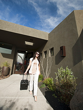 Young woman walking out from home pulling suitcase behind, USA, Utah, St. George
