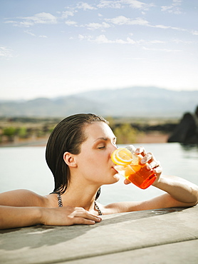 Young attractive woman enjoying cocktail on edge of swimming pool, USA, Utah, St. George