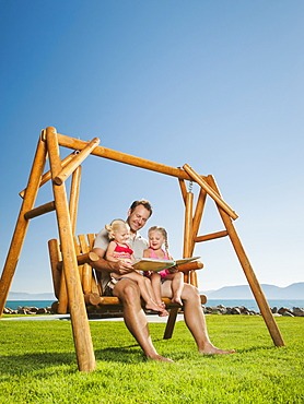 Father with daughters (2-3, 4-5) on swing reading book, USA, Utah, Garden City