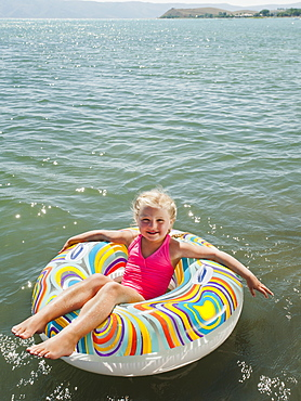 Portrait of girl (4-5) floating on water on inflatable ring