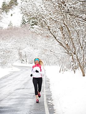 Woman jogging in winter, Salt Lake City, Utah USA