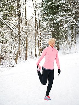 Woman exercising in winter forest, Salt Lake City, Utah USA