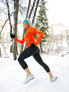 Woman jogging in winter forest, Salt Lake City, Utah USA