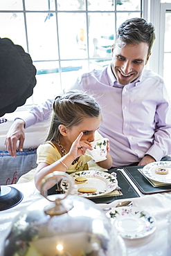 Father and daughter (4-5) eating together in dining room