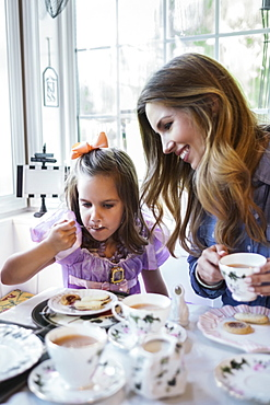 Mother and daughter (4-5) eating together in dining room