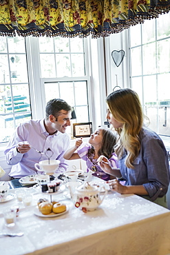 Parents and daughter (4-5) eating together in dining room
