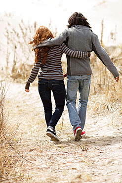 Rear view of couple walking on dirt road