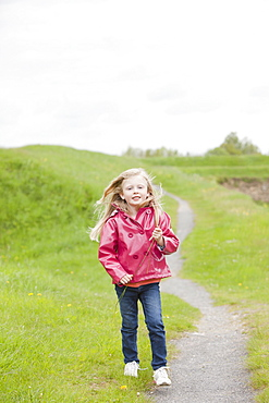 Girl in pink raincoat on country path, France, Rocroi