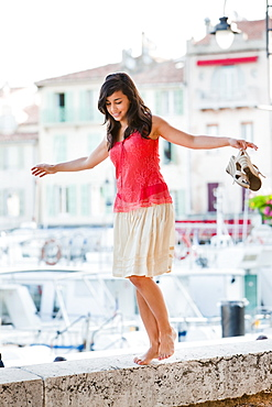 France, Cassis, Young woman balancing on stone wall, France, Cassis