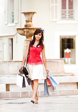 France, Cassis, Young woman carrying shopping bags, France, Cassis