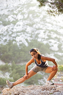 France, Marseille, Young woman stretching on cliff, France, Marseille