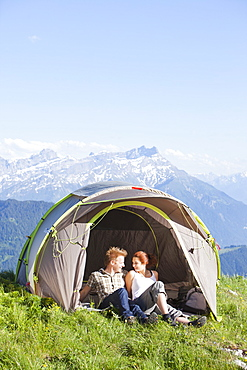 Switzerland, Leysin, Hikers resting in tent pitched on meadow, Switzerland, Leysin