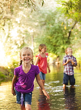 Little girl (4-5) in foreground standing in small stream with friends (6-7), Lehi, Utah