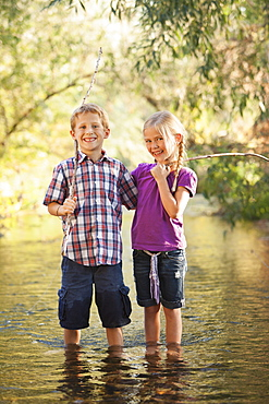 Little boy (6-7) and little girl (4-5) standing together in small steam holding wooden stick fishing poles, Lehi, Utah