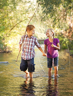 Little boy (6-7) and little girl (4-5) holding hands and walking together in small stream holding wooden stick fishing poles, Lehi, Utah