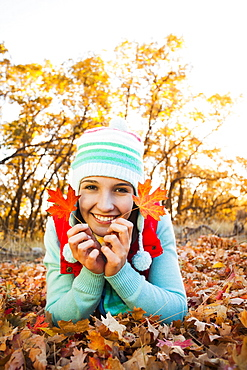 Portrait of smiling young woman lying on autumn leaves, Alpine, Utah