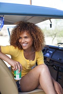 Smiling woman sitting in van