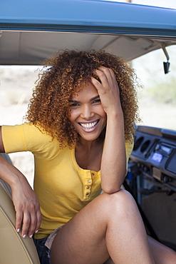 Portrait of smiling woman sitting in van