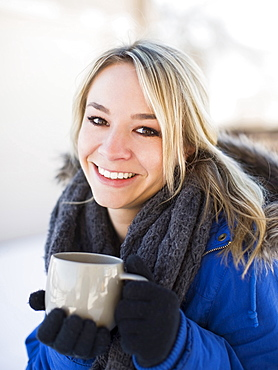 Portrait of woman holding coffee mug outdoors in winter