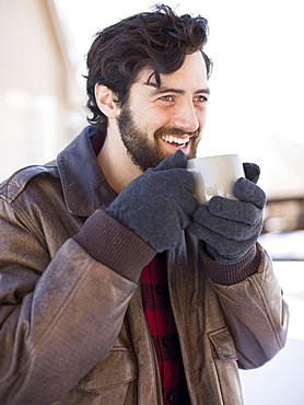 Portrait of man holding coffee mug outdoors in winter