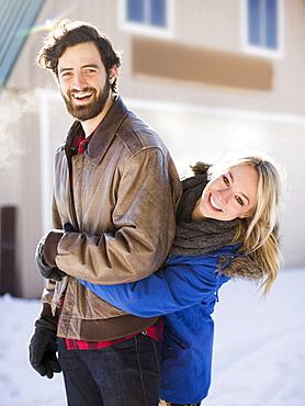 Young woman embracing man in winter, Salt Lake City, Utah