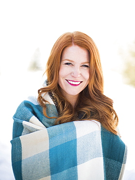 Portrait of mid adult woman wrapped in checked blanket