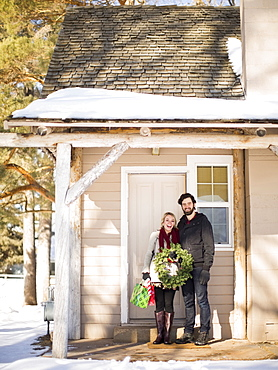 Young couple holding wreath standing in front of house, Salt Lake City, Utah