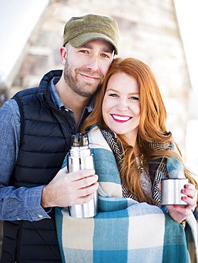Portrait of mid adult couple having drink from vacuum flask, looking at camera