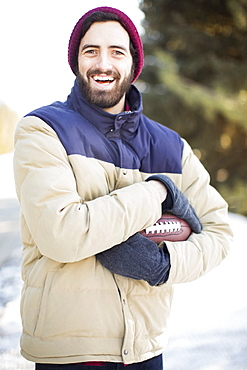 Portrait of man holding football outdoors