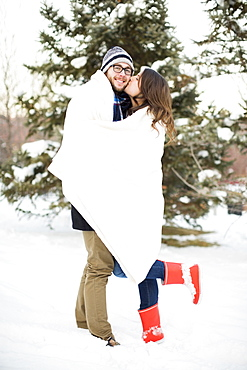 Couple wrapped in blanket standing in snow