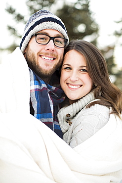 Portrait of couple wrapped in blanket smiling outdoors