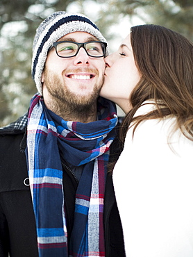 Woman kissing man's cheek outdoors