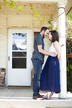 Happy young couple in front of house, USA, Utah, Salt Lake