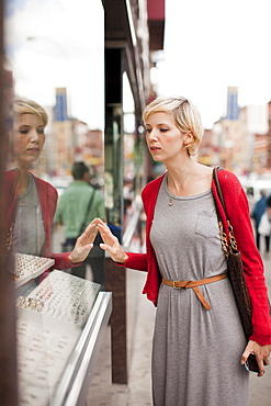 Woman looking at shop display, USA, New York State, New York