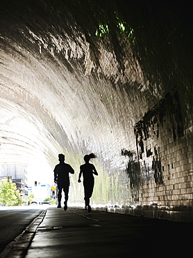 USA, California, Los Angeles, Man and woman running in tunnel, USA, California, Los Angeles