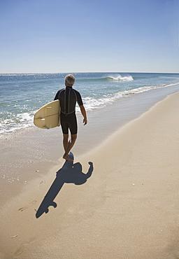 Man carrying surfboard at beach
