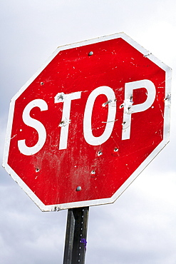 Low angle view of stop sign with bullet holes