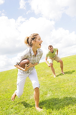Couple playing with football, USA, New Jersey, Mendham
