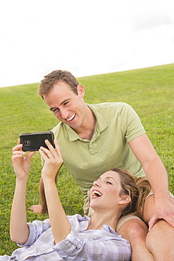 Couple sitting on lawn with camera, USA, New Jersey, Mendham