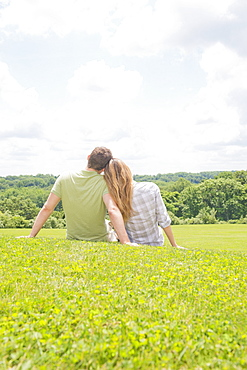 Couple sitting on grass and looking at view, USA, New Jersey, Mendham