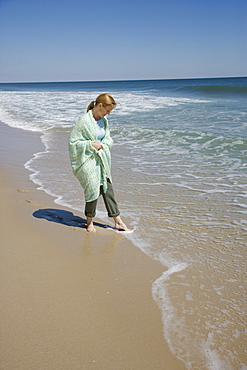 Woman wrapped in blanket at beach